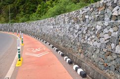 Bicycle lanes stick with the beach. Bicycle lanes stick with the beach and a stone wall along the line stock photo