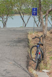 Bicycle lean tree near bicycle path with lake background. Foreign text on the signs is mean `Don`t car pass this way Stock Image