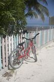 Bicycle leaned up against a colorful picket fence. Beach scene of a bicycle near a picket fence Royalty Free Stock Photo