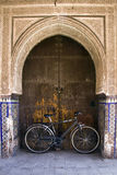 Bicycle leaning against a door under an archway Stock Images