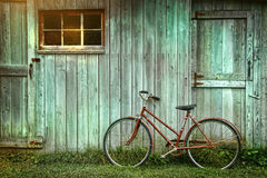 Bicycle leaning against grungy barn