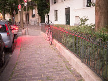 Bicycle leaning against iron fence, bathed in red light from traffic, Montmartre, Paris, early evening. Bicycle leans against iron fence, both bathed in red stock photos