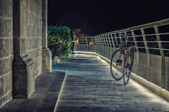 Bicycle leaning against a lit railing. In front of an old church at night Stock Photography