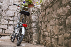 Bicycle leaning against an old stone wall Stock Photo