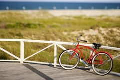 Bicycle leaning against rail on beach. stock photo