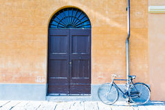 A bicycle leaning against the wall next to a door Royalty Free Stock Photography