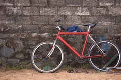 Bicycle leaning against wall. Red bicycle leaning against wall outdoors stock photos