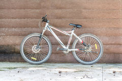 Bicycle leaning against a wooden wall Royalty Free Stock Image