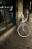 Bicycle leaning on building. Closeup of bicycle leaning on urban building with glass window Royalty Free Stock Photos