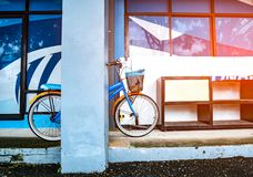 Bicycle leaning on a pole near a wooden shoe rack placed on a cement floor in a building. With flare light. Vintage style royalty free stock photos
