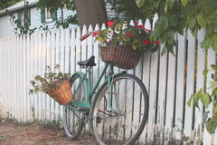 Bicycle Leaning on a White Picket Fence. Old fashioned ladies bicycle with baskets of flowers leaning against a white picket fence stock photos
