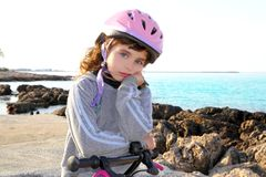 Bicycle little pensive girl in rocky beach Stock Images