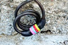 A bicycle lock with colorful number combinations. A metal wire with a combination lock hanged before a wall which is worn out Stock Image