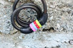 A bicycle lock with colorful number combinations. A metal wire with a combination lock hanged before a wall which is worn out Royalty Free Stock Photo