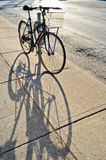 Bicycle locked to the rack and its shadow Royalty Free Stock Images