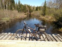 Bicycle on logging bridge over river stock photography