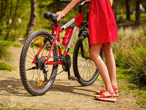 Bicycle and low section female legs by girl in park. Stock Photo