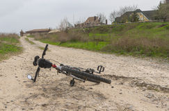 Bicycle lying on a bad macadam country road. Old bicycle lying on a bad macadam country road Stock Photography
