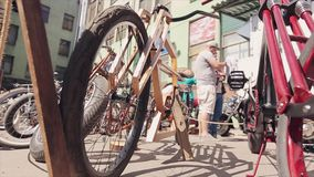 Bicycle made of wooden boards stand with other in line on street. Sunny summer day. People. Exhibition stock video