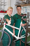 Bicycle mechanic and apprentice repairing a bike Stock Images