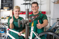 Bicycle mechanic and apprentice repairing a bike Royalty Free Stock Photos