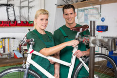 Bicycle mechanic and apprentice repairing a bike Stock Image
