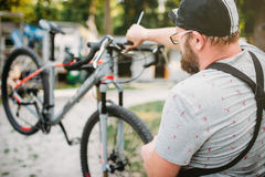 Bicycle mechanic in apron adjusts bike outdoor. Professional bicycle mechanic in apron adjusts bike. Cycle workshop outdoor. Bicycling sport, bearded service man Stock Photo