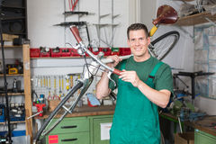 Bicycle mechanic carrying a bike in workshop Stock Image