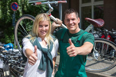 Bicycle mechanic and customer in bike store giving thumbs up Stock Photos