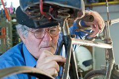 Bicycle mechanic fixing the brakes. Bicycle mechanic fixing brakes with tool Stock Photos