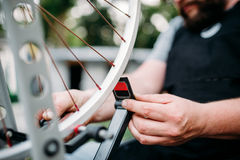 Bicycle mechanic hands repair wheel closeup. Professional bicycle mechanic hands adjusts bike spokes and repair wheel with service tools closeup. Cycle workshop stock photography