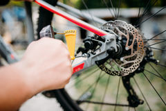 Bicycle mechanic hands with service tools. Bicycle mechanic hands adjusts with service tools back disk brakes. Cycle workshop outdoor. Bicycling sport, repairman royalty free stock photos
