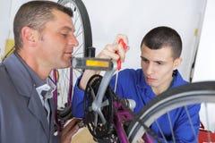 Bicycle mechanic learning to fix bike. Bicycle mechanic learning to fix a bike Stock Photos