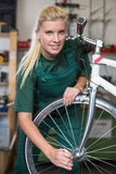 Bicycle mechanic repairing wheel on bike in a workshop Stock Images