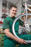 Bicycle mechanic repairing wheel on bike in a workshop Royalty Free Stock Images
