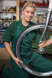 Bicycle mechanic repairing wheel on bike in a workshop Stock Image