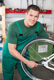 Bicycle mechanic repairing wheel on bike Royalty Free Stock Image