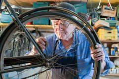 Bicycle mechanic at work. Bicycle mechanic who olia a wheel Royalty Free Stock Images