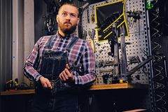 Bicycle mechanic in a workshop with bike parts on background. royalty free stock image