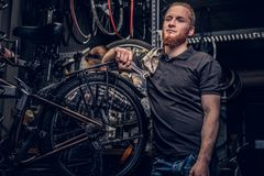 Bicycle mechanic in a workshop with bike parts and wheel on a background. stock images