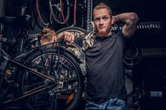Bicycle mechanic in a workshop with bike parts and wheel on a background. royalty free stock photography