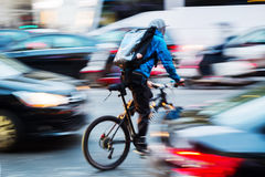 Bicycle messenger in busy city traffic. Picture of a bicycle messenger in busy city traffic with camera made motion blur effect Stock Images
