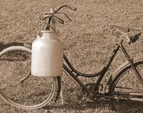 Bicycle milkman with the old bin cans and sepia effect. Ancient bicycle milkman with the old bin of aluminum cans and sepia effect Royalty Free Stock Image