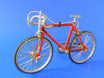 Bicycle model. Small-scale model of a red bicycle isolated on blue Stock Photography