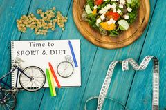Bicycle model, salad of fresh vegetables, notepad with text & x22;Time to SPORT & DIET& x22;, stopwatch and tape measure. On a blue wooden table Stock Photo
