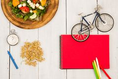 bicycle model, salad of fresh vegetables, red notepad, stopwatch stock photo