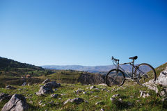 Bicycle On Mountain. Bicycle Parked On Field Against Mountains royalty free stock photos