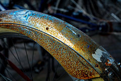 Bicycle mudguard with rust and remnants of stickers, detail, abs. Rust and remnants of stickers on a bicycle mudguard, abstract dark background with bright Stock Photo