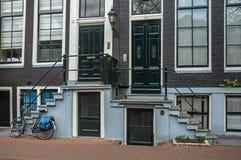 Bicycle na frente das escadas às portas de entrada de construções elegantes em Amsterdão Imagens de Stock Royalty Free