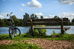 Bicycle near bench and pond in park Royalty Free Stock Photos